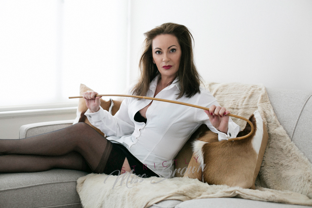 professional domme and headmistress strictly miss brown reclines in her london studio